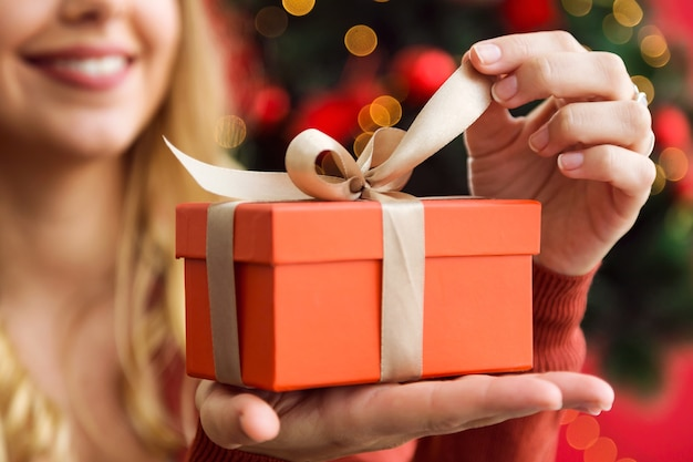 Woman opening a orange gift