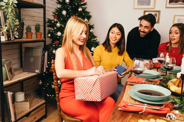 Woman opening present box at christmas dinner