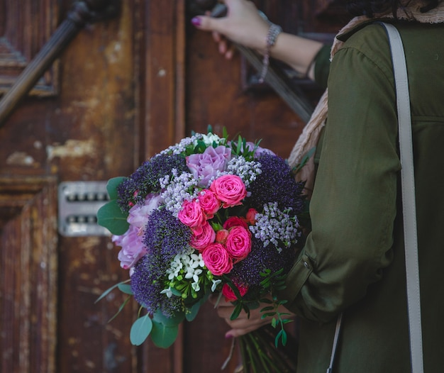 A woman opening, pushing the door with a bouquet of flowers on the other hand