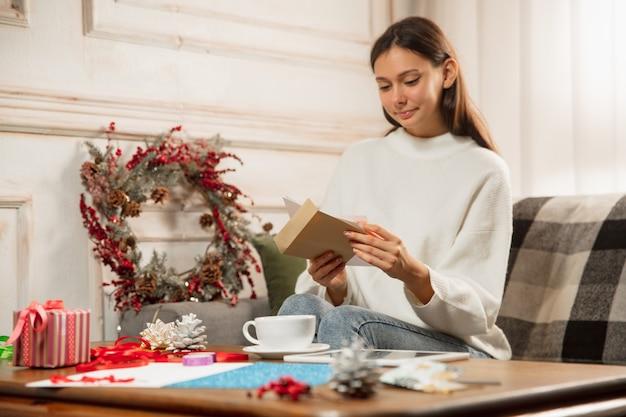 友人や家族から2021年の新年とクリスマスのグリーティングカードを受け取る女性を開く