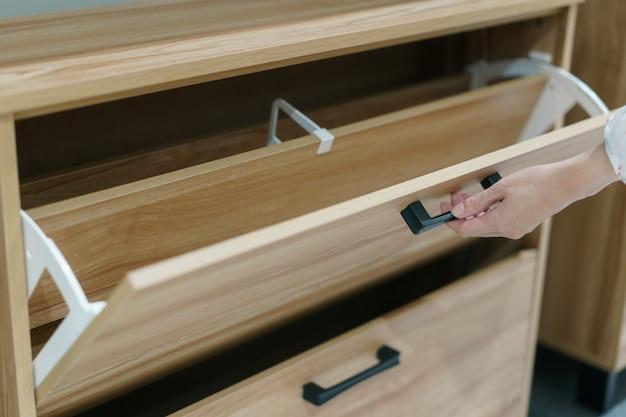 Женщина открывает деревянный шкаф для хранения обуви