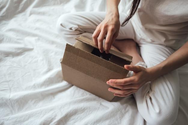 Женщина открывает картонную коробку, сверток сидит на кровати дома. концепция доставки