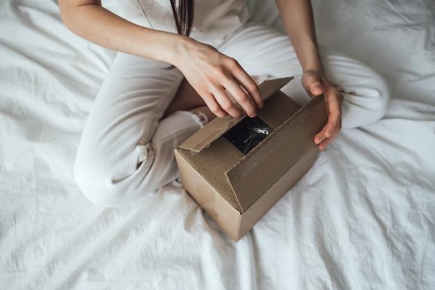 여자는 골판지 상자를 엽니 다. 소포는 집에서 침대에 앉아 있습니다. 배달 개념