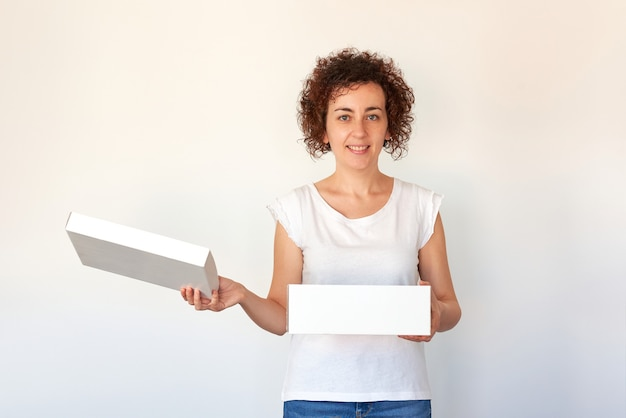 Женщина открывает обувную коробку на изолированном белом фоне