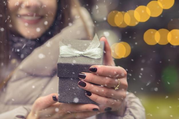 女性は降雪時にボケの光で通りに弓で小さなギフトボックスを開きます