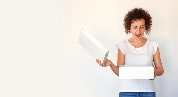 Женщина открывает белую коробку на изолированном белом фоне с выражением удивления и радости