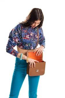 Woman opens brown handbag. bright pants and crop top. all things in place. stylish look for summer.
