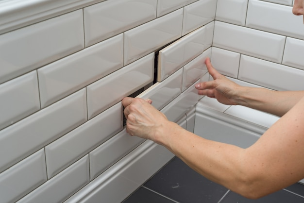 Woman opens, closes the hidden revision sanitary hatch on the wall
