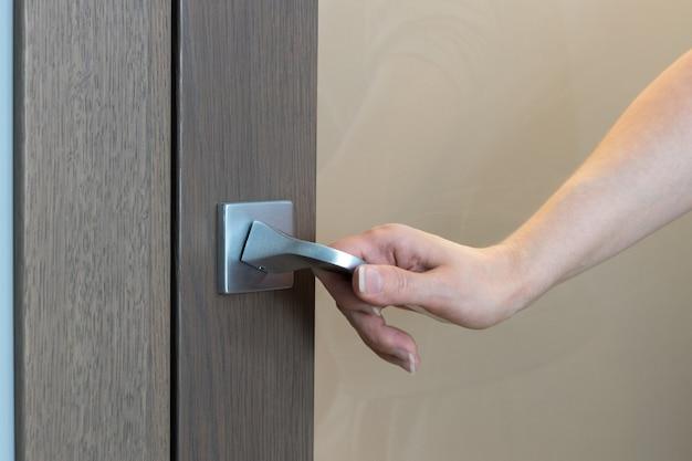 여자는 문을 열거 나 닫습니다. 손 여는 문, 인식 할 수없는 사람의 근접 촬영. 손만 보입니다.