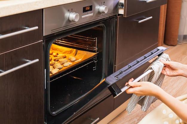女性はハロウィーンのためにクッキーが焼かれるオーブンを開きます。