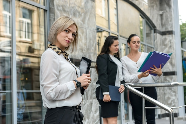 Woman opposite her colleagues showing information on tablet, another two standing behind