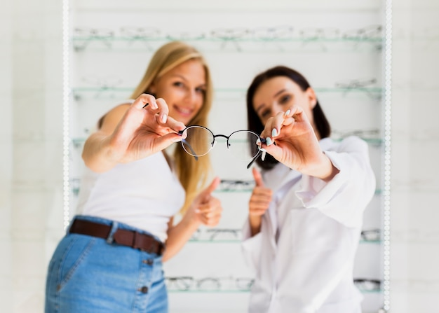 Woman and optician holding eyeglasses frame