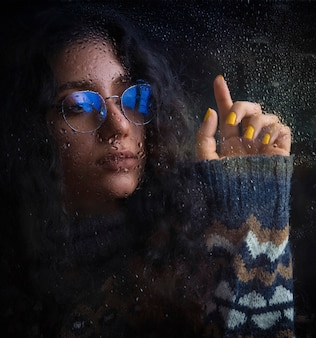 Woman in optique glasses with blue shadow and warm knit jacket