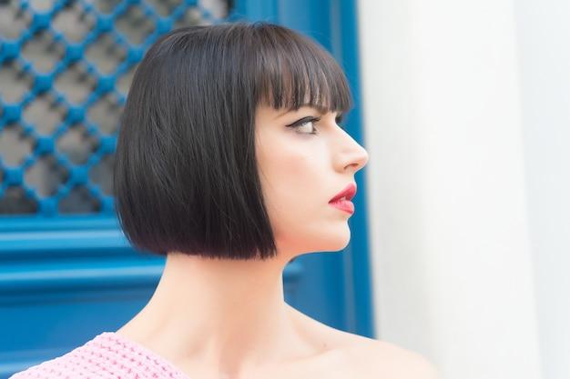 赤い唇のメイクの顔のプロファイル、パリのブルネットの髪、青いドアのフランスの女性または女の子。美しさ、見た目、顔。ファッション、スタイルのコンセプト。