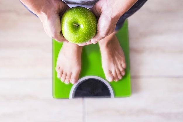 Женщина или мужчина на весах, показывающих яблоко, и выбирают его образ жизни - концепция хорошего питания