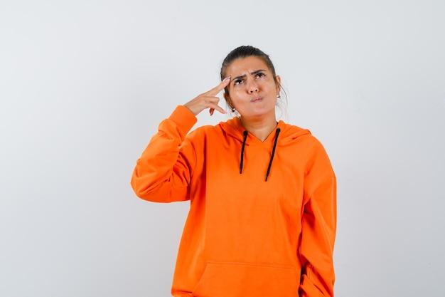 Donna in felpa arancione che tiene le dita sulle tempie e sembra pensierosa pensi