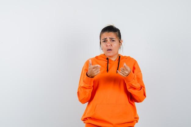 Donna in felpa con cappuccio arancione che punta alla telecamera e sembra perplessa