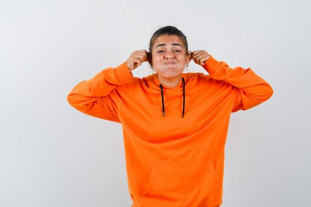 Donna in felpa con cappuccio arancione che si tira le orecchie e sembra divertente