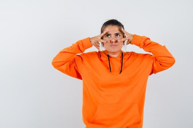 Donna in felpa con cappuccio arancione che mostra il segno a v sugli occhi e sembra esitante
