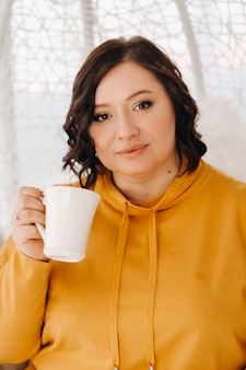 A woman in an orange hoodie sits in an unusual chair and drinks coffee at home.
