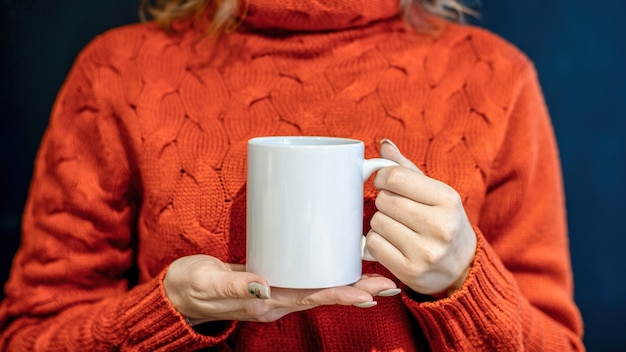 Woman in orange sweater holding a white cup with both hands,