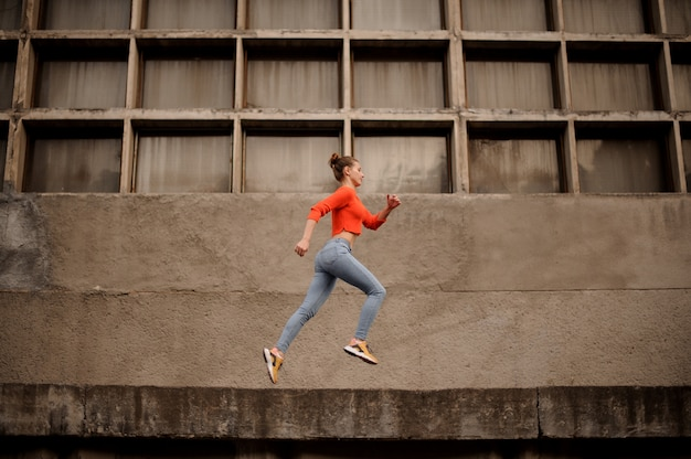 Woman in the orange sweater and jeans running on the concrete construction
