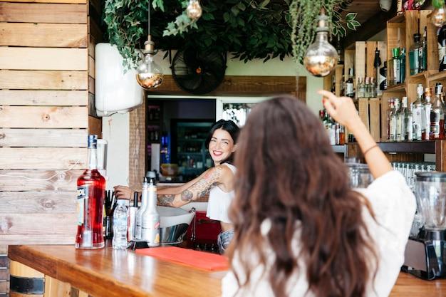 Женщина заказывает в баре