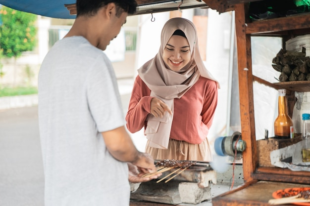 屋台の食べ物の売り手でチキンサテを注文する女性