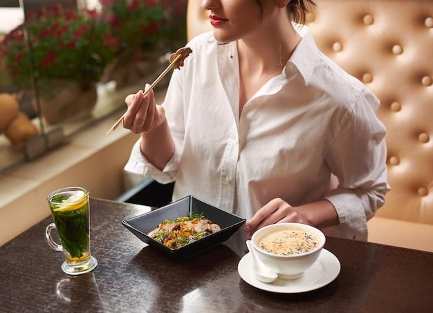 Женщина заказывает еду в восточном стиле в ресторане.