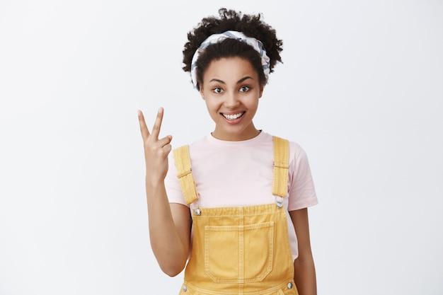Женщина заказывает два напитка в баре. портрет стильной симпатичной африканской девушки в модных желтых дунагаре и повязке на голову, демонстрирующей жест победы и улыбающейся с дружелюбным выражением лица
