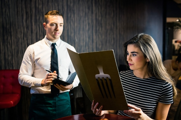 Woman ordering to waiter from the menu in a restaurant