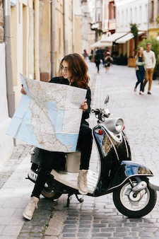 Woman in original sunglasses sits on the scooter with touristic map