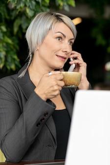 Женщина на улице наслаждается кофе и разговаривает по телефону
