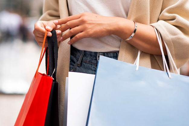Женщина выходит за покупками, держа в руках много сумок