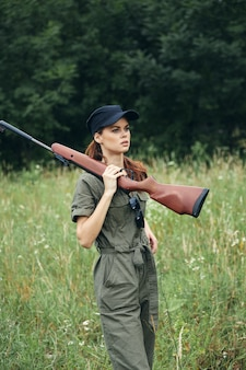 Woman on outdoor arms in the hands of a green jumpsuit lifestyle fresh air black cap green trees on