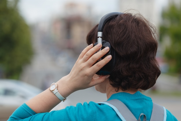 Woman outdoor in the city listening music with headphones