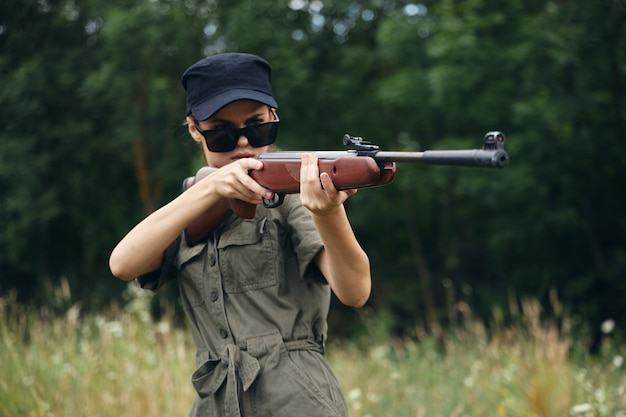 Woman on outdoor fresh air is aimed with weapons in nature green leaves