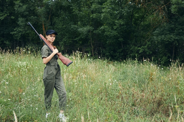 Woman on outdoor green jumpsuit black cap weapons