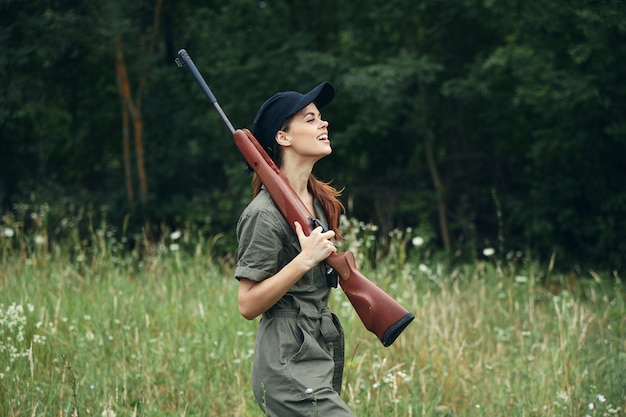 Woman on outdoor side view of holding a weapon in the hands of a green jumpsuit black cap forest background
