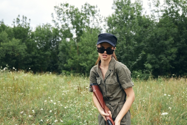 Woman on outdoor sunglasses  gun green leaves  trees