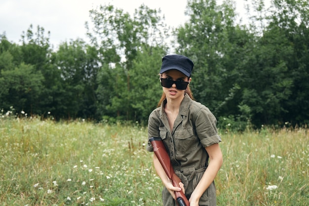 Woman on outdoor sunglasses with fresh air gun green leaves green trees