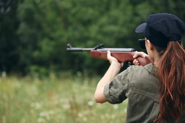 Woman on outdoor weapon in hand sight hunting nature fresh air close-up