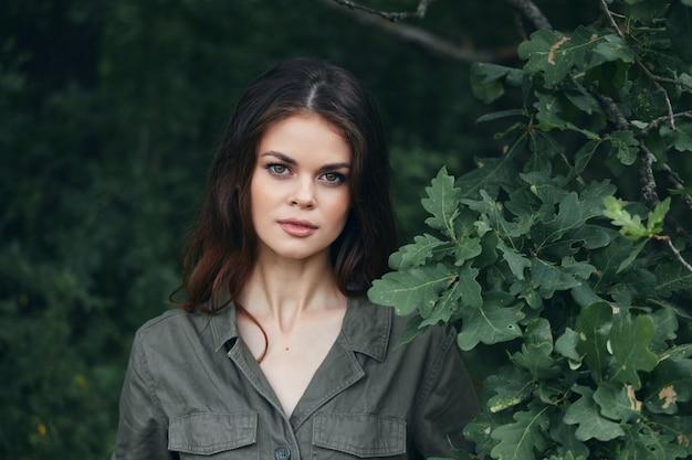 여자 야외에서 매력적인 모습 녹색 나뭇잎 관목 여름 클로즈업