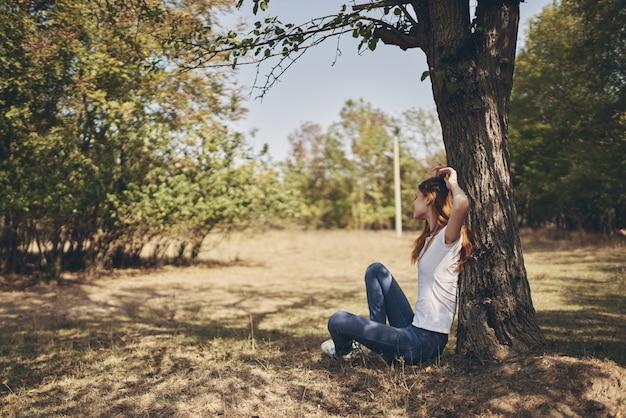 木の太陽の自由の旅で屋外の女性 Premium写真