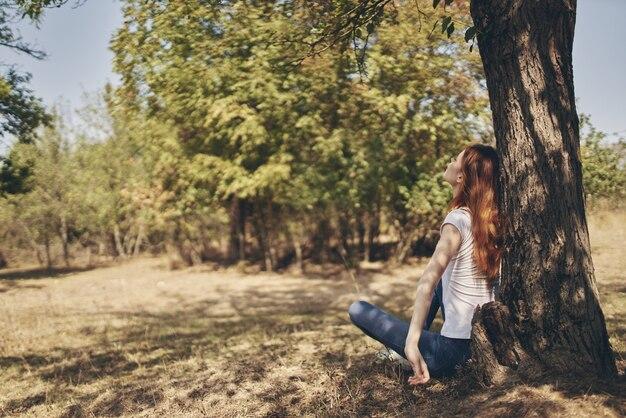 木の太陽の自由の旅で屋外の女性