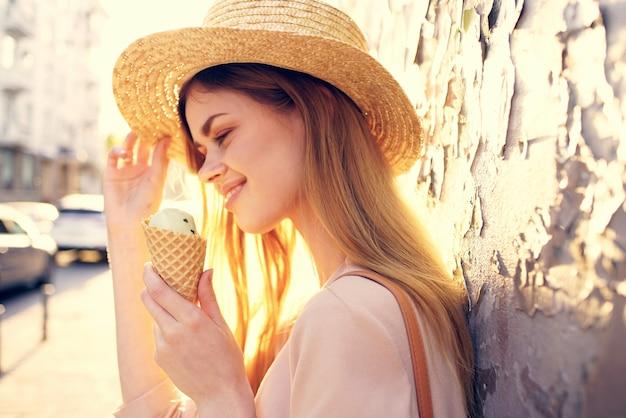屋外でアイスクリームを食べる女性晴れた日の散歩。高品質の写真