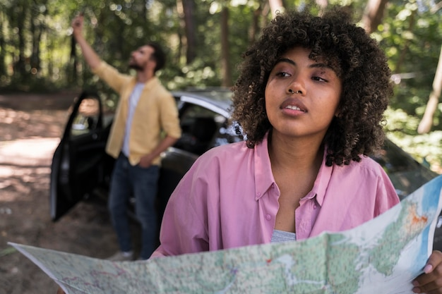 Woman outdoors holding map while boyfriend takes selfie next to car