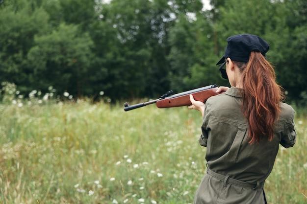 Женщина на открытом воздухе держит оружие в руках