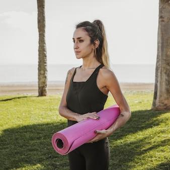 Woman outdoors holding yoga mat