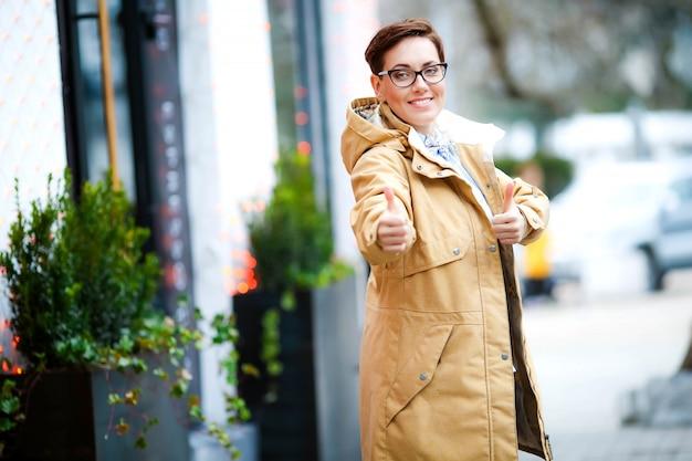 屋外のレインコートと路上でメガネの女性